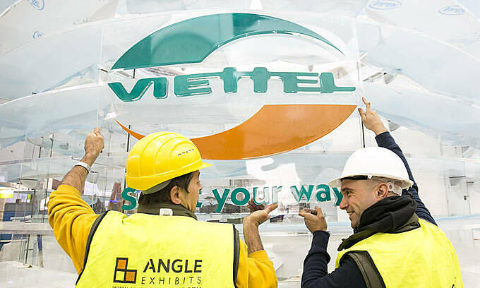 Two workers put up Viettel sign outside an office. Photo courtesy of Viettel.